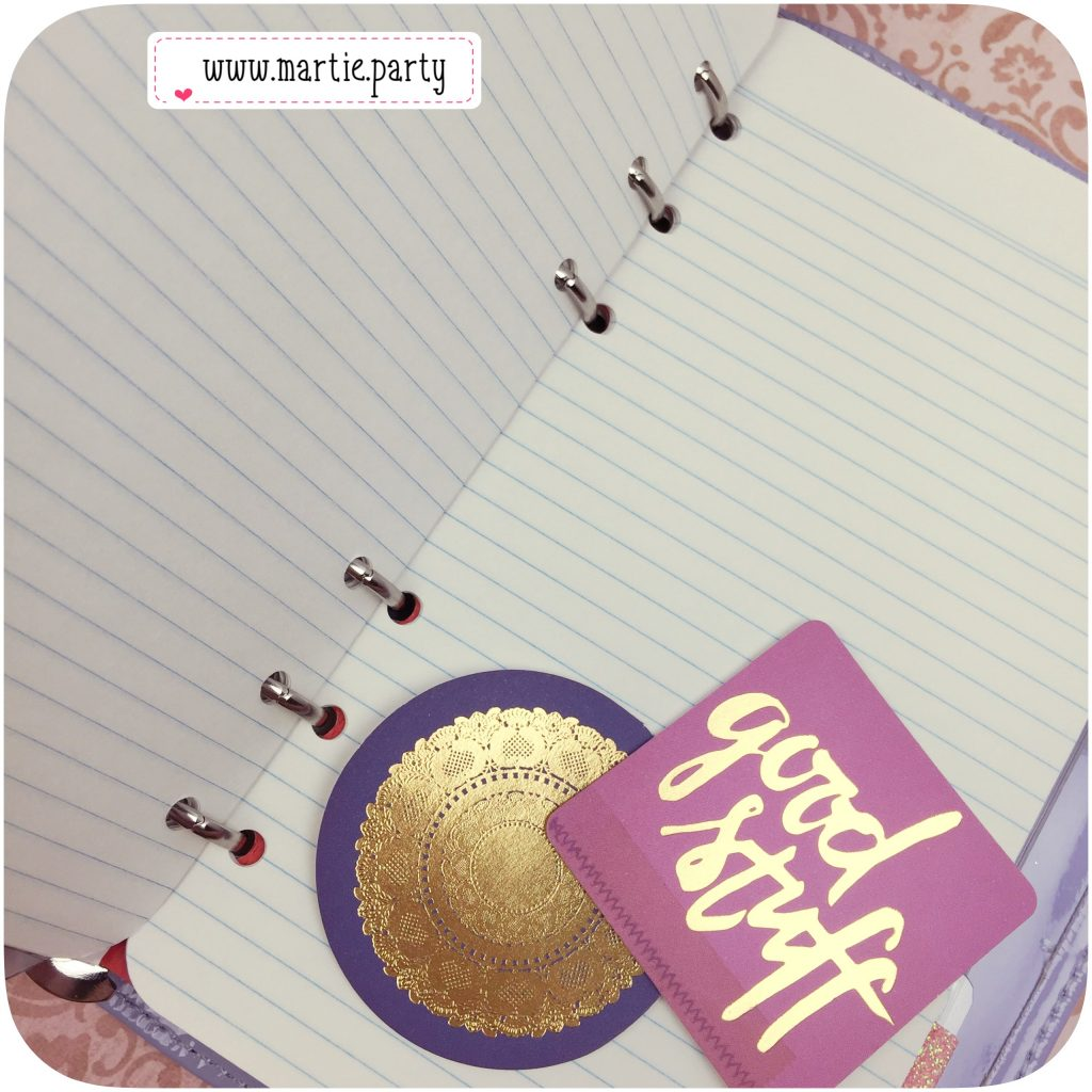 Blank note pages in a planner with decorative embellishments.