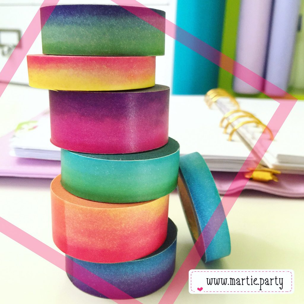 Rainbow watercolour washi stack on a desk.