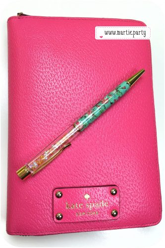 Pink Kate Spade Wellesley planner with pen atop.
