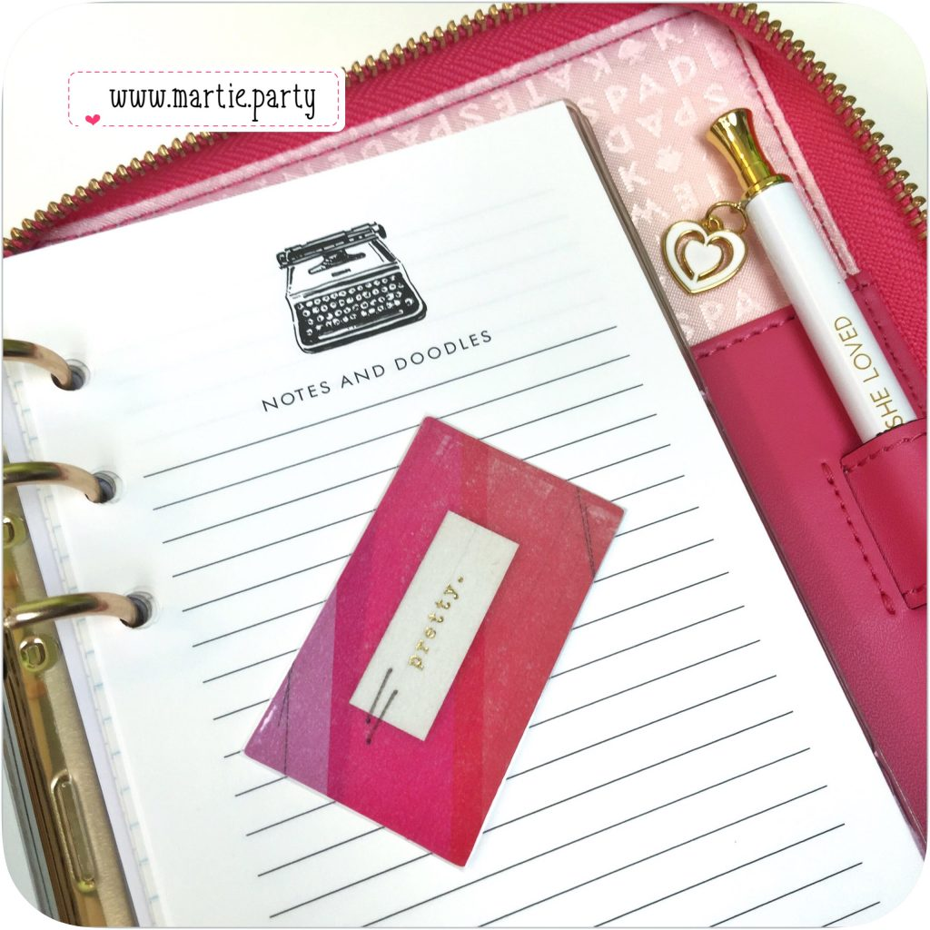 Opened Kate Spade Wellesley planner with lined paper and pen.