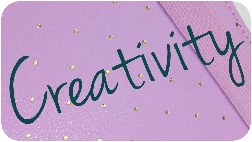 """Creativity"" written atop a planner."